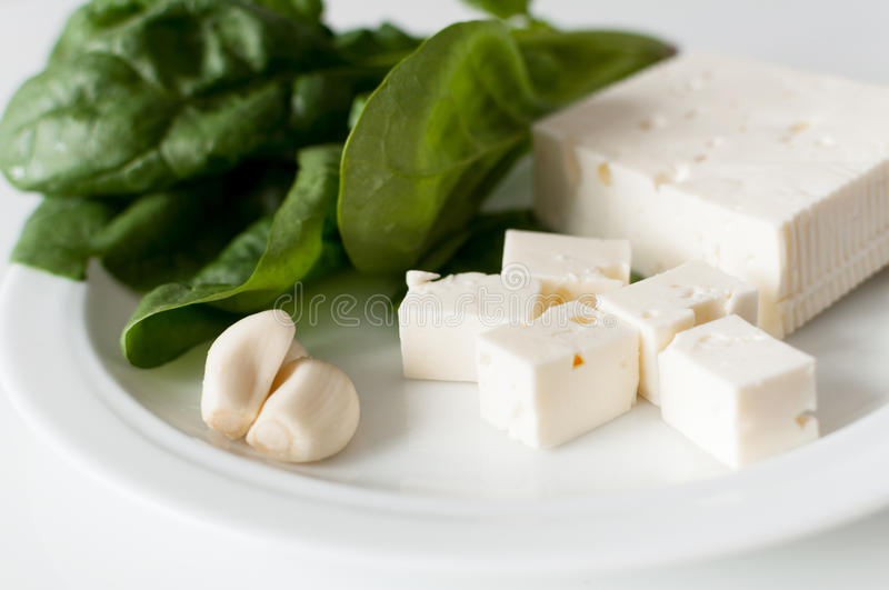 Feta cheese and spinach. Fresh spinach leaves, feta cheese and garlic cloves on a white plate royalty free stock image