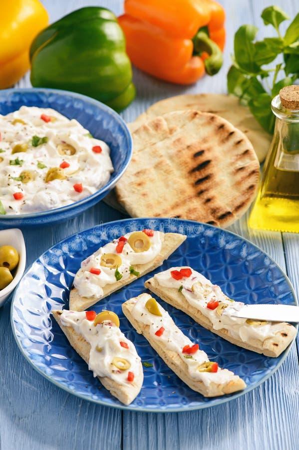 Feta-kaas met olijven wordt en peper met pitabroodje wordt gediend uitgespreid dat Griekse stijlschotel royalty-vrije stock fotografie