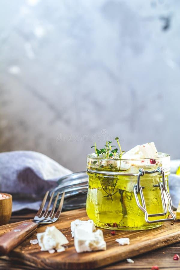 Feta mariniert im Olivenöl im Glasgefäß lizenzfreie stockbilder