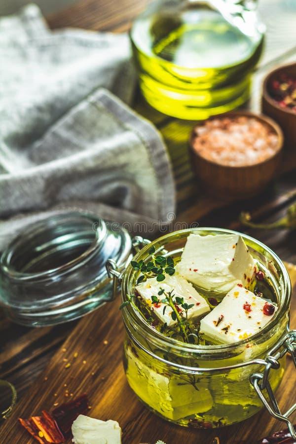 Feta mariniert im Olivenöl mit frischen Kräutern im Glasgefäß stockfotos