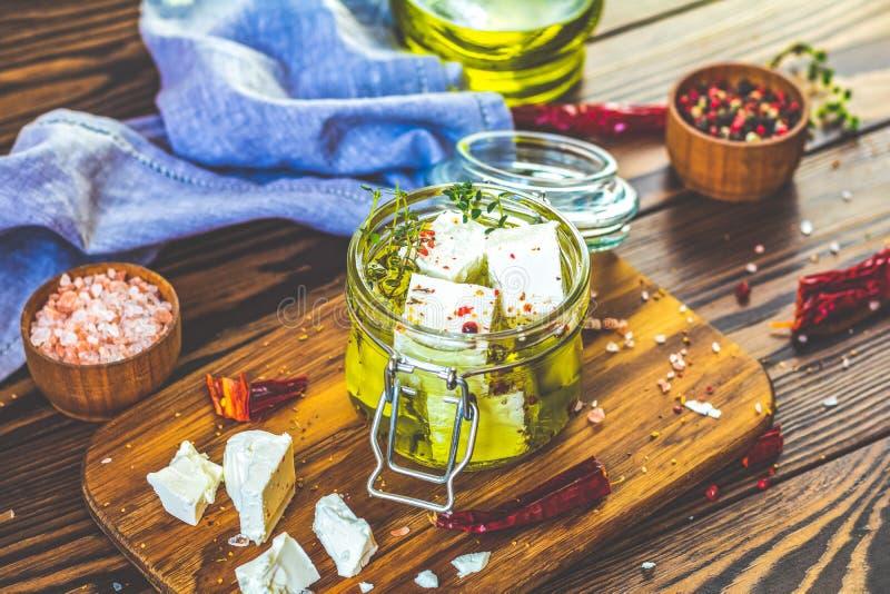 Feta mariniert im Olivenöl mit frischen Kräutern im Glasgefäß lizenzfreies stockfoto