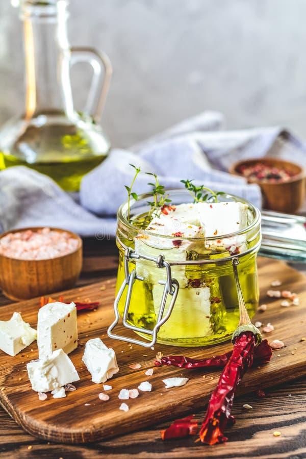 Feta mariniert im Olivenöl mit frischen Kräutern im Glasgefäß lizenzfreie stockfotografie