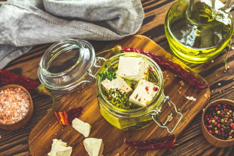 Feta mariniert im Olivenöl mit frischen Kräutern im Glasgefäß lizenzfreie stockfotos