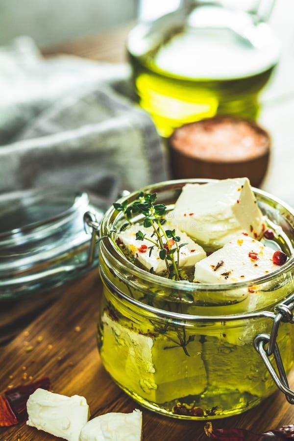 Feta mariniert im Olivenöl mit frischen Kräutern im Glasgefäß lizenzfreies stockbild