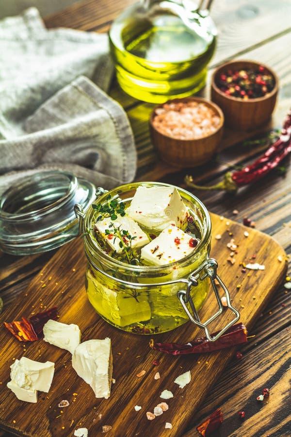 Feta mariniert im Olivenöl mit Gewürzen stockfotos