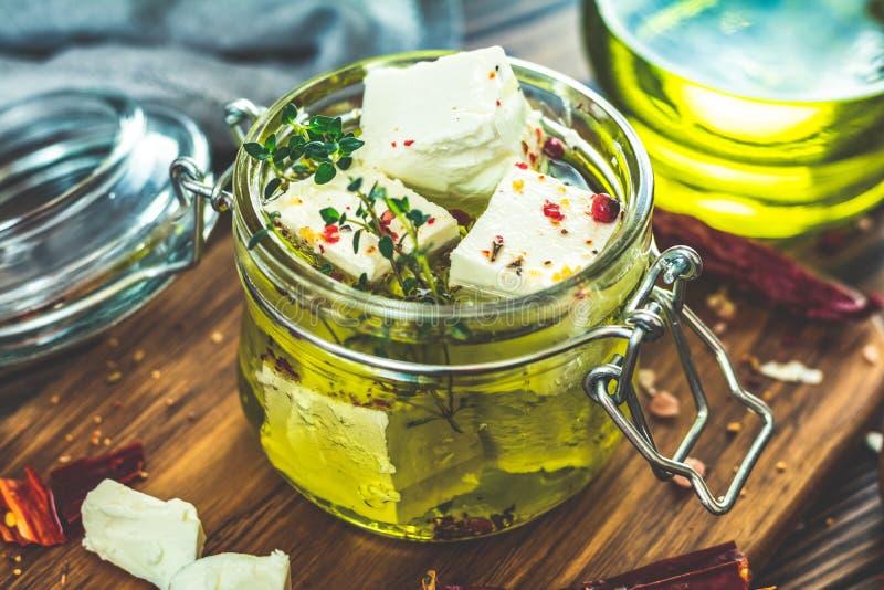 Feta mariniert im Olivenöl mit Gewürzen stockfotografie