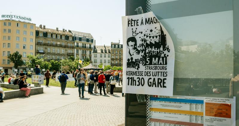 Fete a Macron. STRASBOURG, FRANCE - MAY 5, 2018: People making a party protest Fete a Macron in front of Gare de Strasbourg poster calling to party stock photo