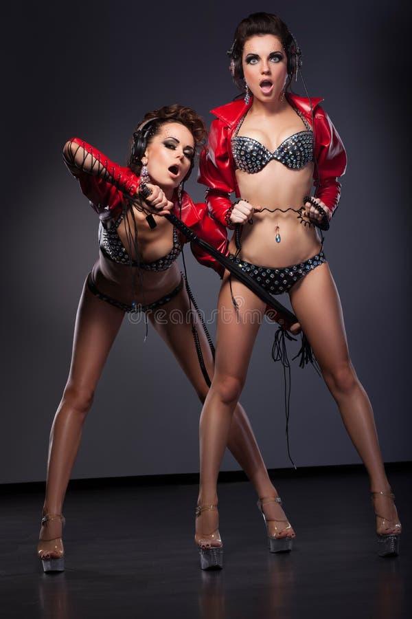 Fetiche. Mujeres atractivas divertidas en actitud erótica con el azote. Entusiasmo imagen de archivo