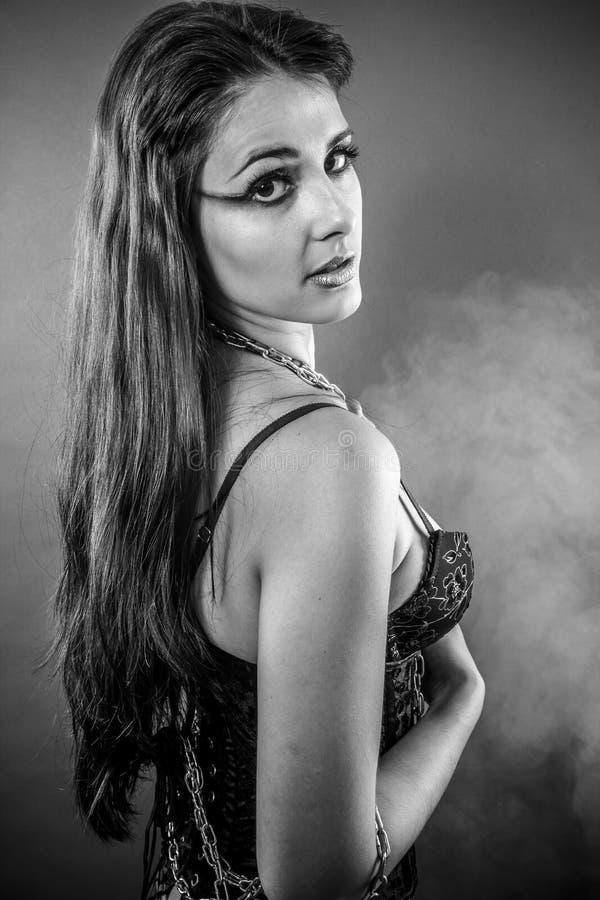 Fetisch, schöner Brunette kleidete im Schwarzen mit großem Eisen Chai an lizenzfreie stockfotografie