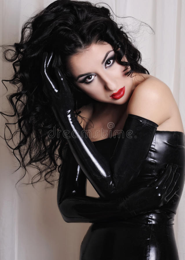 Fetish model posing in black latex outfit stock photo