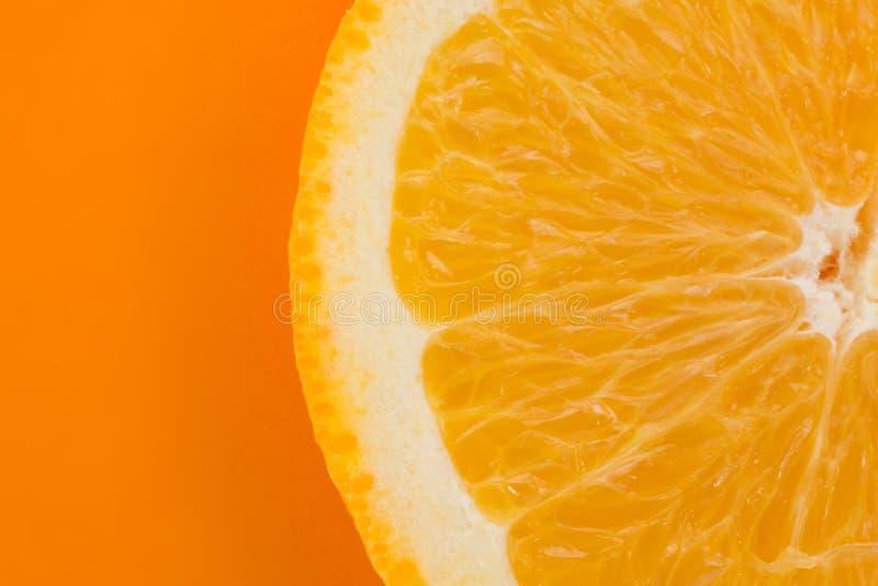 Fetta arancio su un fondo arancio fotografie stock