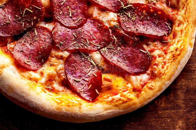 Fetta calda con le merguez, formaggio di fusione della pizza su una fine di legno rustica della tavola su Vista superiore fotografie stock