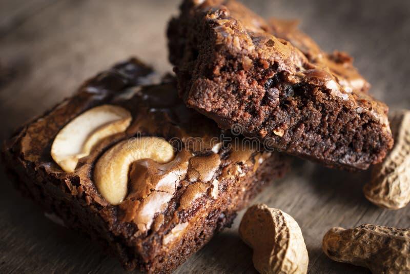 Fetta del brownie due con la guarnizione l'anacardio e delle arachidi disposti accanto  fotografie stock libere da diritti
