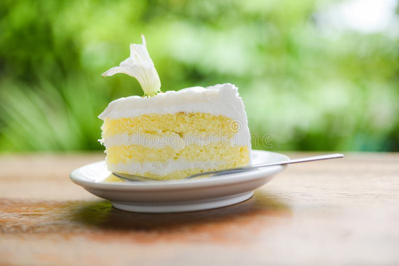 Fetta del dolce su palte bianco con il fiore sul fondo di legno della natura della tavola - dolce di noce di cocco delizioso immagine stock