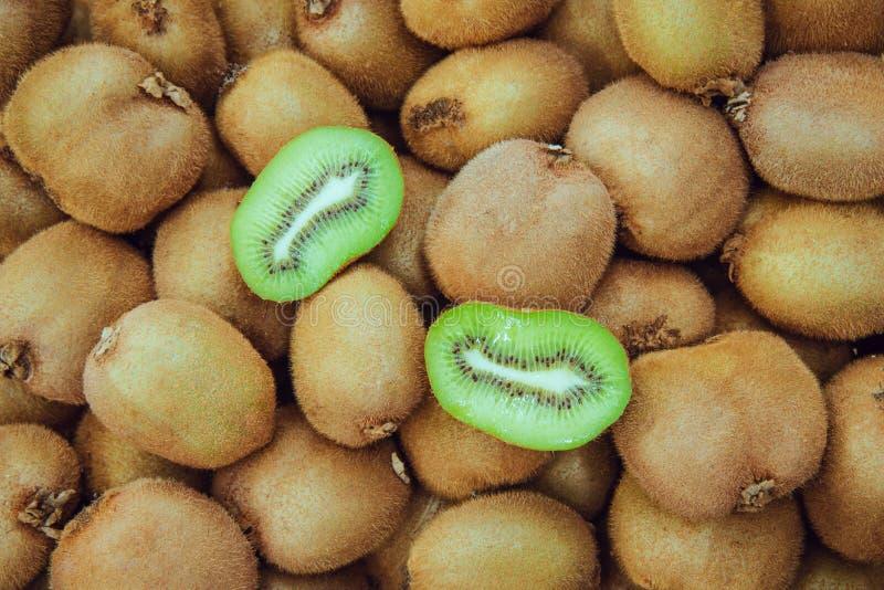 Fetta del kiwi fra molti interi kiwi fotografia stock libera da diritti