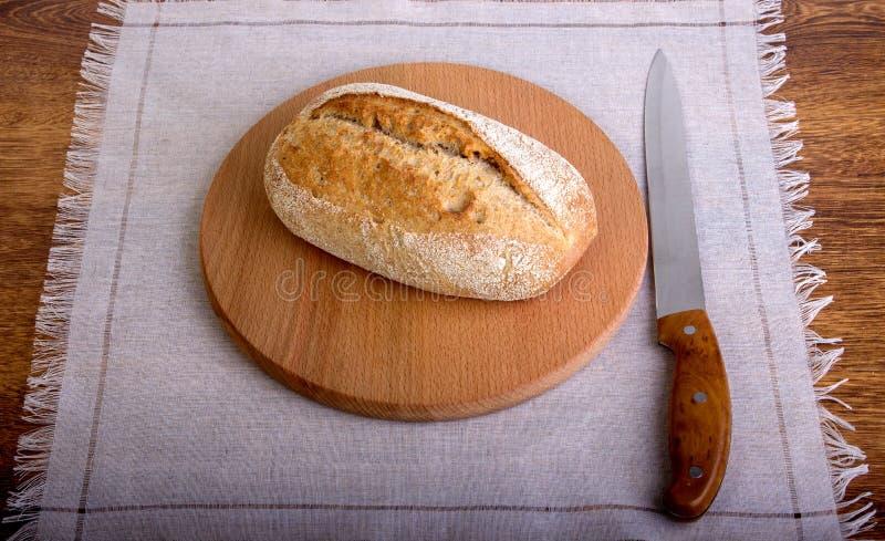 Fetta del pane fresco e coltello di taglio sulla tavola immagini stock libere da diritti