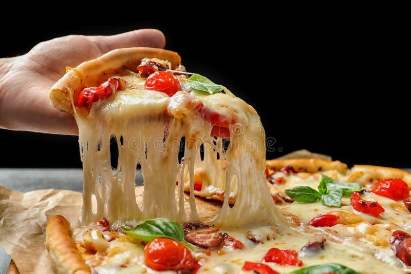 Fetta della tenuta della donna di pizza calda deliziosa sopra la tavola, fotografia stock