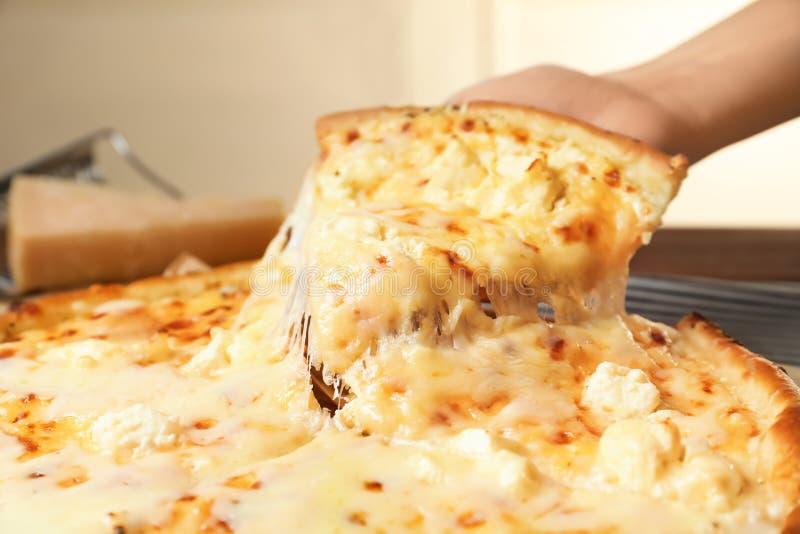 Fetta della tenuta della donna di pizza calda deliziosa sopra tabl, primo piano fotografia stock libera da diritti