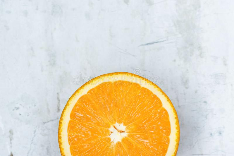 Fetta di arancia viva vibrante succosa matura di colore su Gray Stone Concrete Metal Background Manifesto di alta risoluzione del fotografia stock