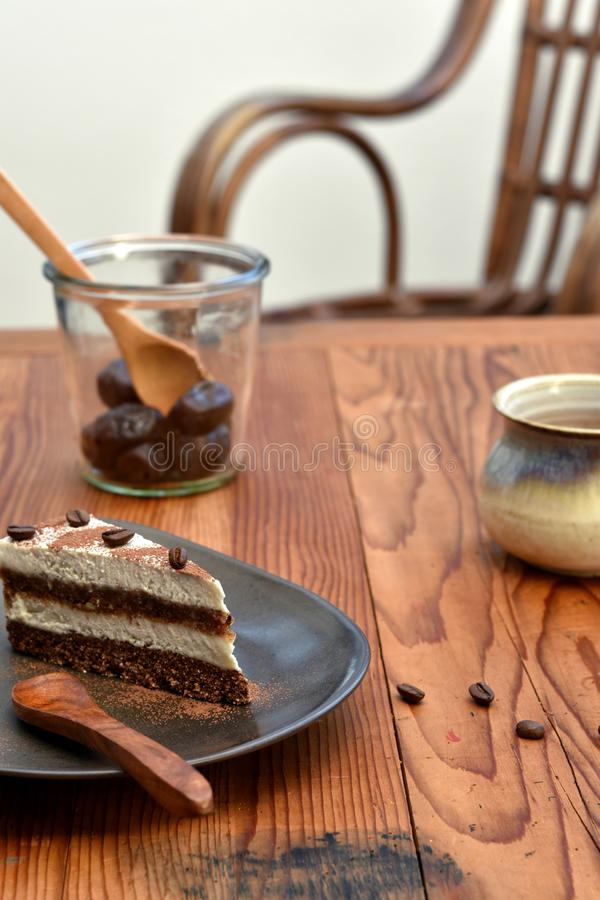 Fetta di dolce crudo di tiramisù su un piatto marrone immagine stock