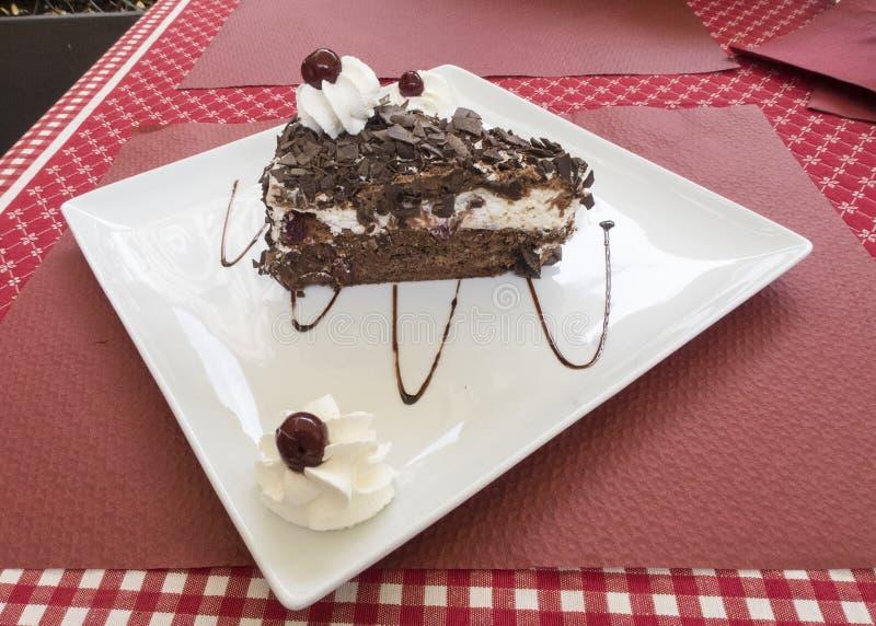 Fetta di dolce della foresta nera su un piatto bianco su una tavola immagine stock