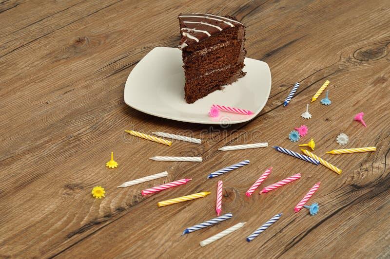 Fetta di dolce di cioccolato con le candele di giorno di nascita fotografia stock