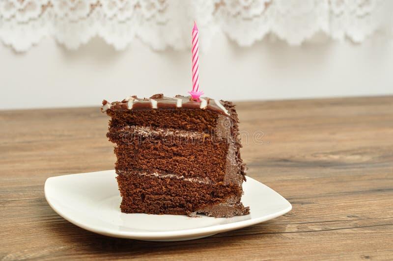 Fetta di dolce di cioccolato con una candela rosa di compleanno immagine stock
