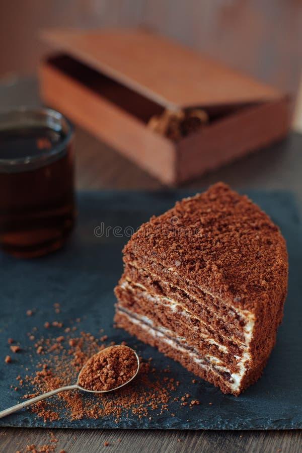 Fetta di dolce di miele e di tazza stratificati di tè sul bordo nero dell'ardesia Vista superiore Due parti Fuoco selettivo fotografia stock
