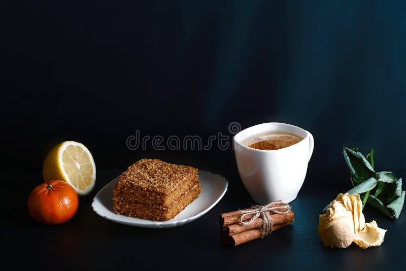 Fetta di dolce di miele stratificato Medovik decorata con la stella dell'anice sul piatto bianco, bastoni di cannella, una tazza  immagini stock