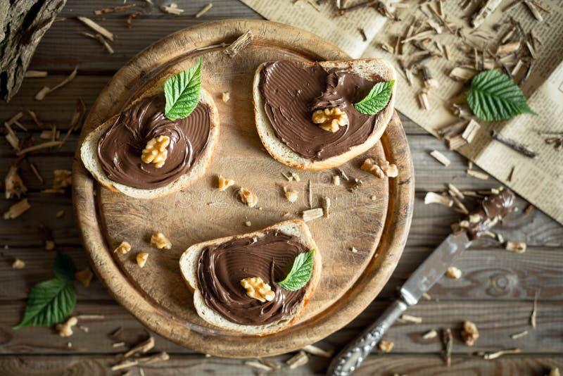 Fetta di pane con la crema ed i dadi del cioccolato Cioccolato spanto con il coltello fotografia stock