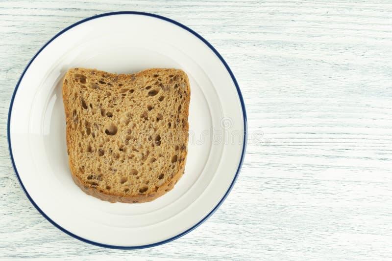 Fetta di pane del grano con la muffa Su un piatto bianco con una banda blu Su una tabella di legno immagine stock