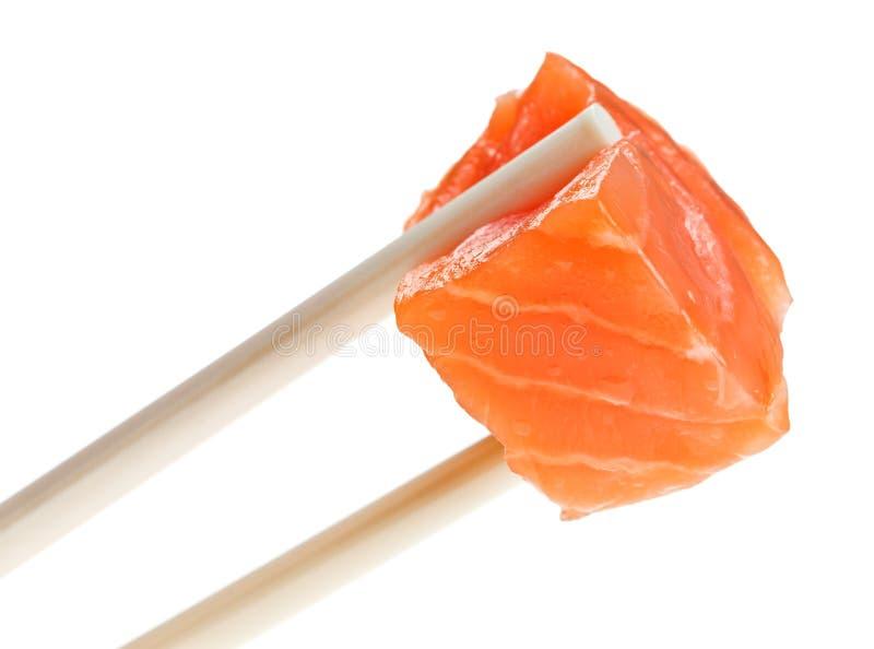 Fetta di pesci dei salmoni rossi in bacchette immagine stock libera da diritti