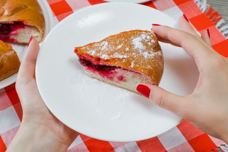 Fetta di pezzo squisito di dolce della ciliegia con zucchero poedered in donna fotografie stock