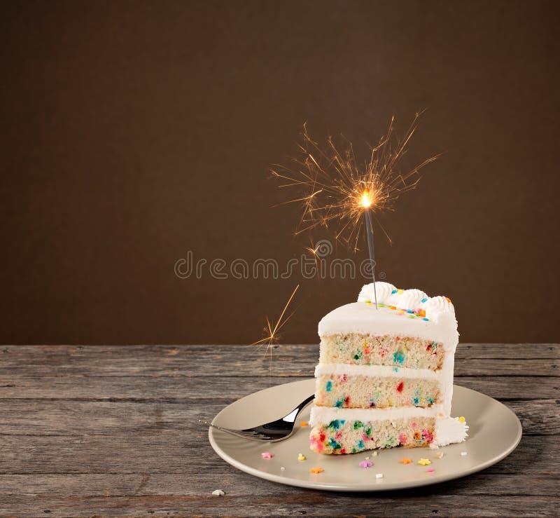 Fetta di torta di compleanno con la stella filante immagini stock libere da diritti