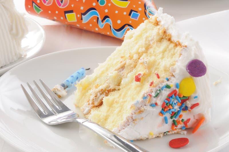 Fetta di torta di compleanno e di cappello del partito immagini stock libere da diritti