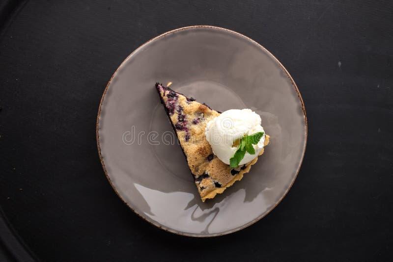 Fetta di torta di mirtillo con gelato alla vaniglia sul piatto grigio su fondo nero immagini stock libere da diritti