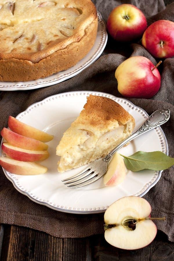 Fetta fresca di torta di mele con l'intera torta nel fondo immagine stock