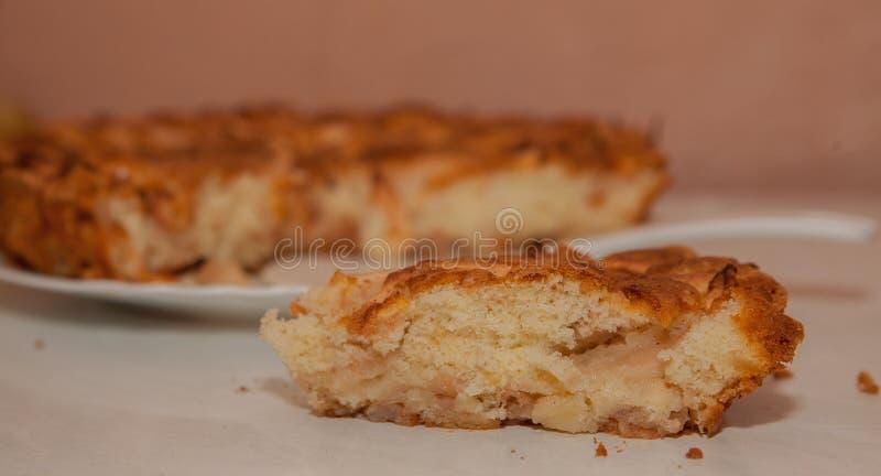 Fetta fresca di torta di mele con l'intera torta nel fondo fotografia stock libera da diritti