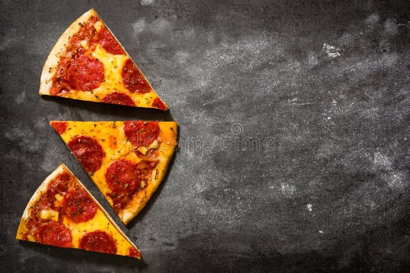 Fetta italiana calda della pizza di merguez sulla pietra nera immagine stock libera da diritti