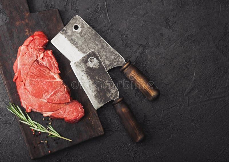 Fetta organica cruda fresca di raccordo di brasatura della bistecca sul tagliere con gli scuri della carne su fondo di pietra ner fotografia stock libera da diritti