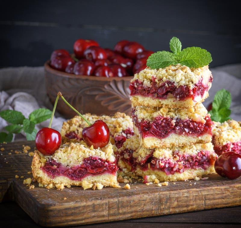 Fetta quadrata di torta della briciola con la ciliegia fotografie stock