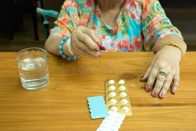 Fette ältere Frauenhand des Gesundheitswesenkonzeptes, die Pillen und glas hält lizenzfreie stockfotos