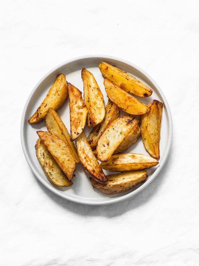 Fette al forno rustiche semplici della patata su un fondo leggero, vista superiore fotografia stock libera da diritti