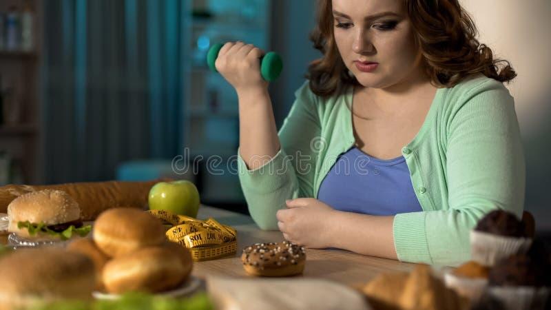 Fette Dame, die mit Dummkopf trainiert und süßen Donut, nährende Willenskraft betrachtet lizenzfreie stockfotos