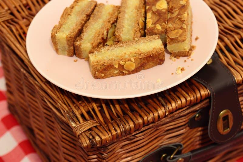 Fette del dolce della mandorla su un piatto con un canestro di picnic immagine stock