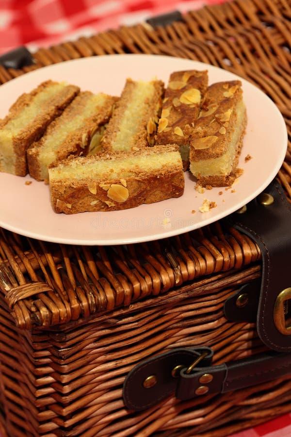 Fette del dolce della mandorla su un piatto con un canestro di picnic immagine stock libera da diritti