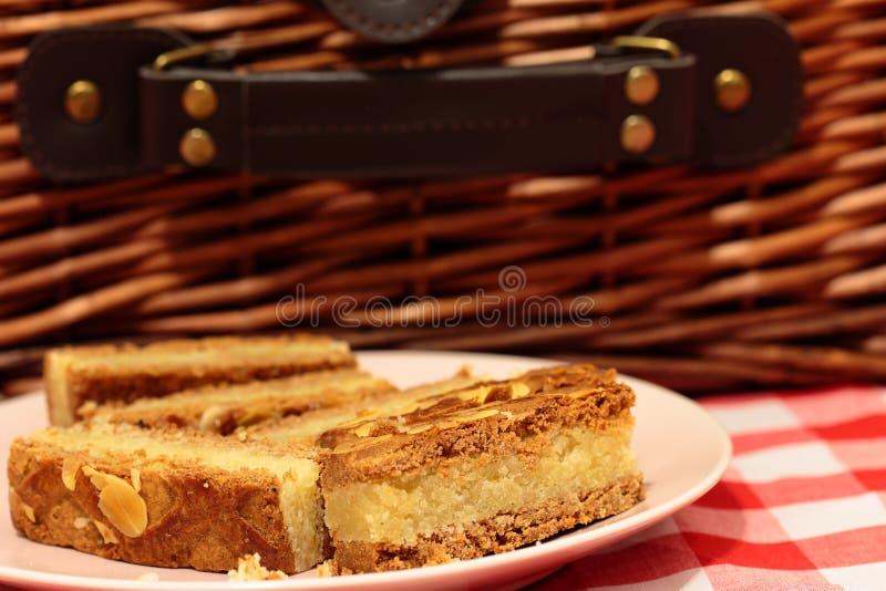 Fette del dolce della mandorla su un piatto con un canestro di picnic fotografia stock