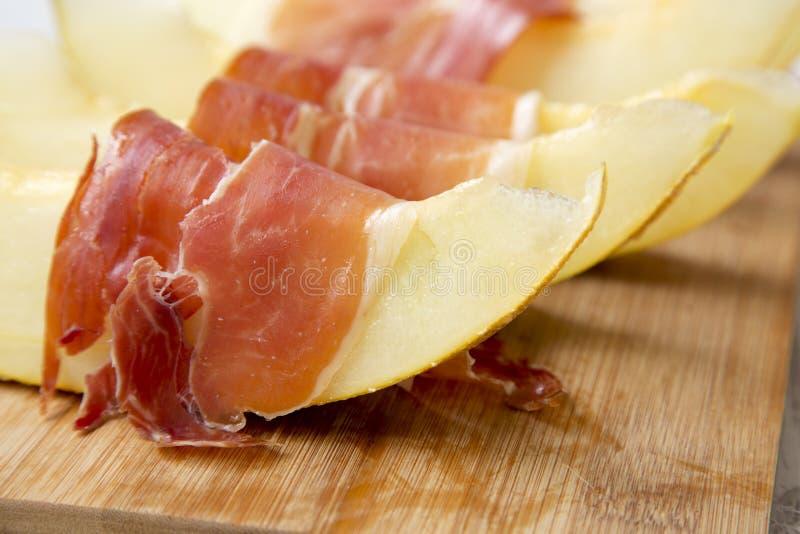 Fette del melone avvolte in prosciutto di Parma fotografie stock