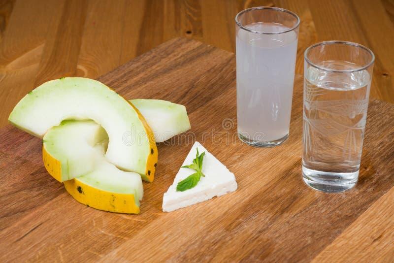 Fette del melone e feta e menta con il raki immagini stock