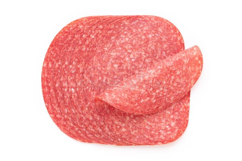 Fette del salame su fondo bianco immagini stock